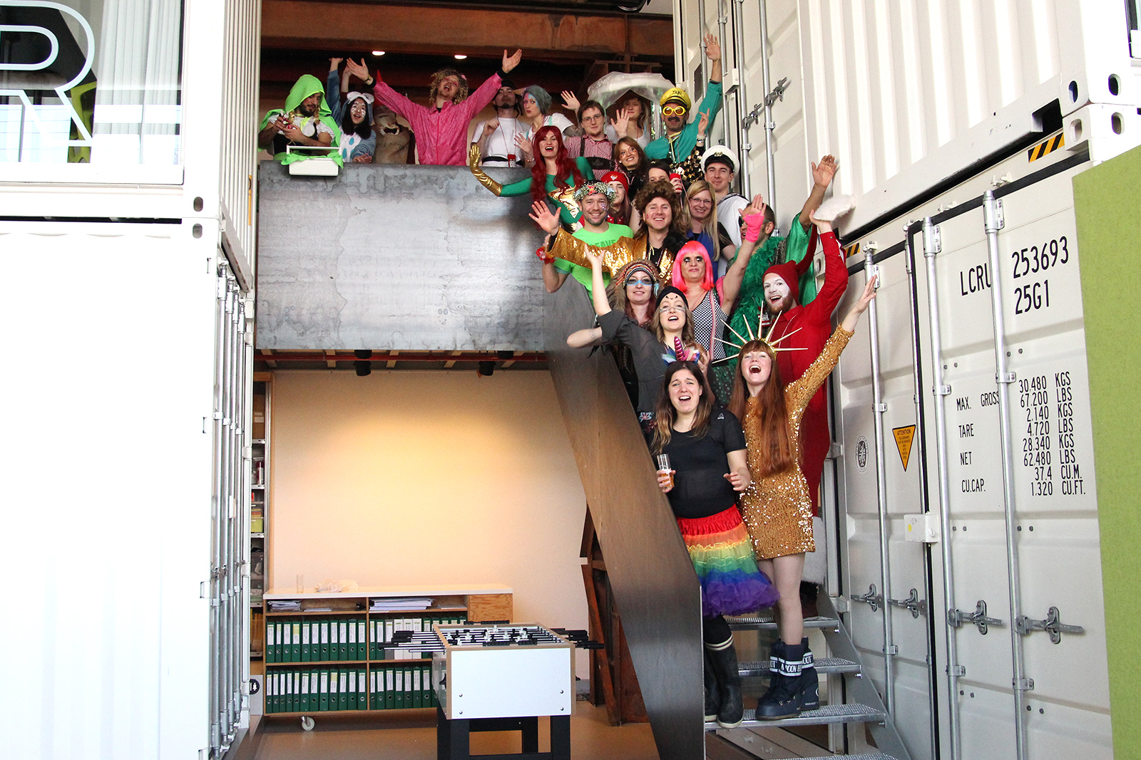 Photo Salon K all employees dressed up on stairs hands up