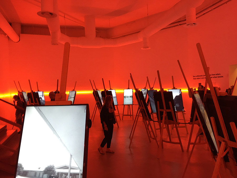 photo exhibition hall red light wooden easels with illuminated black and white pictures