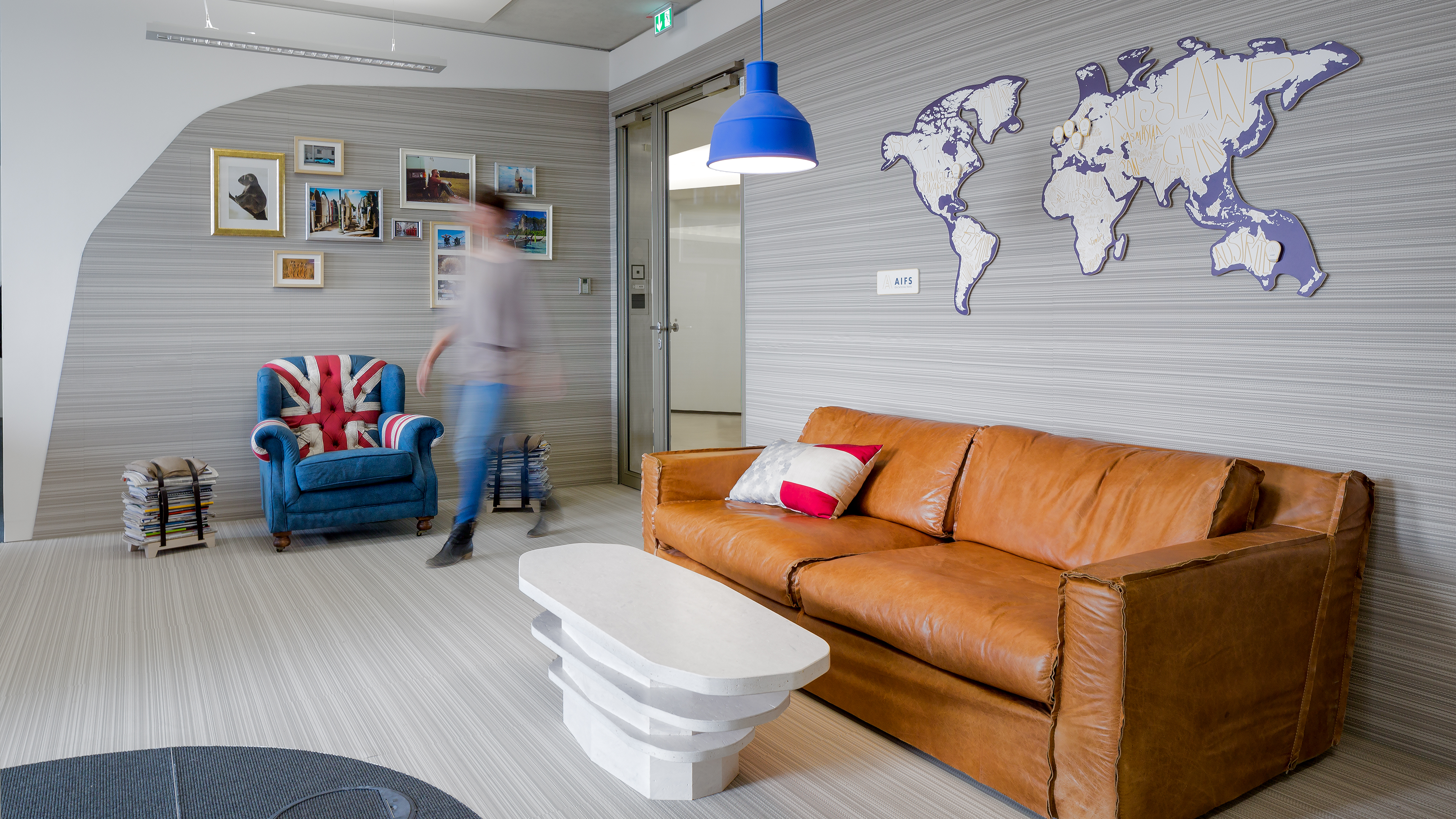 Comfortable entrance area with leather sofa and armchair, coloured lampshades and travel photos