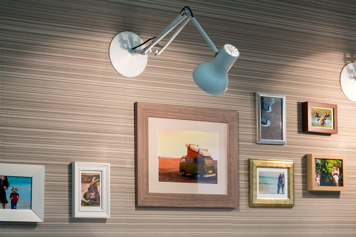 Wall with warm brown striped wallpaper. Light blue lamp and holiday pictures.