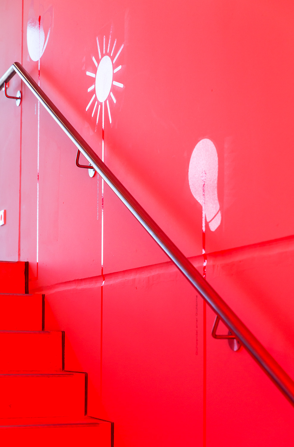 Red staircase with white graphics on the wall
