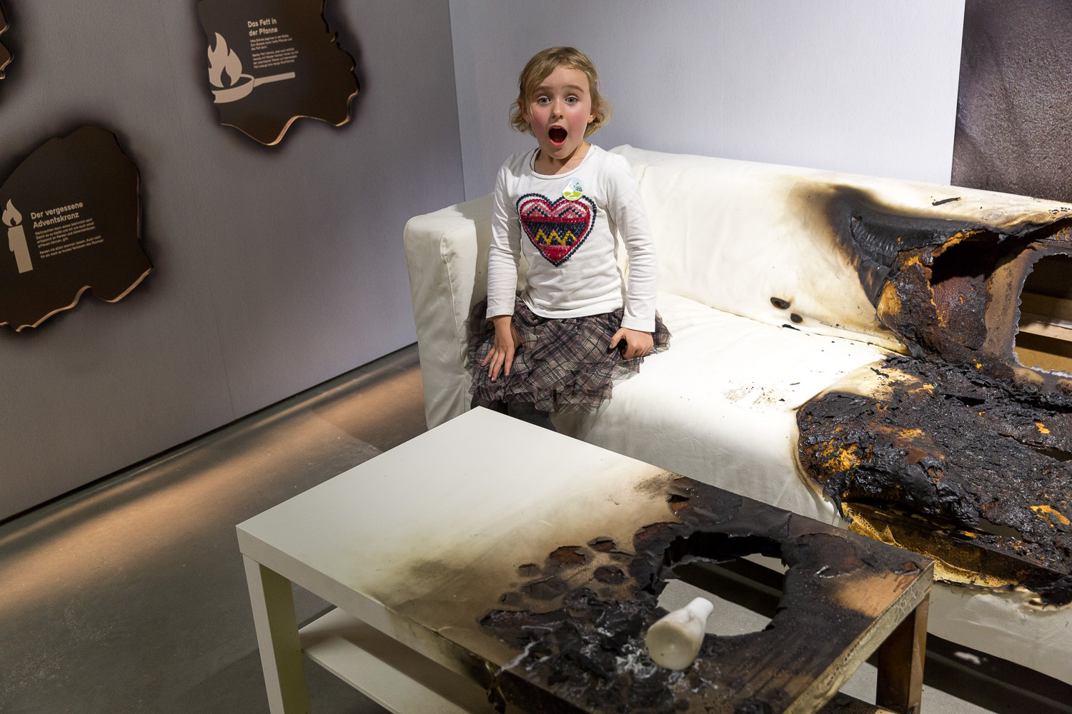 Surprised child sits on half burnt sofa