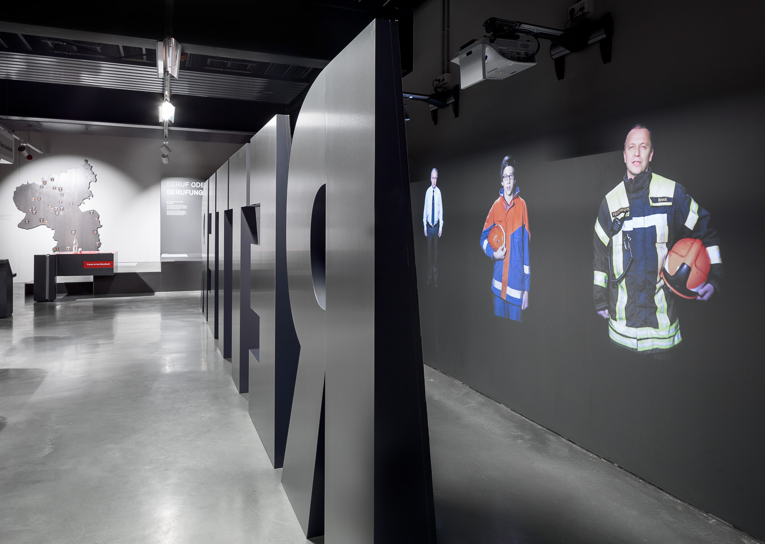 "Large black letters form the word ""rescuers"" and serve as room divider. Behind them are projections of various firefighters."