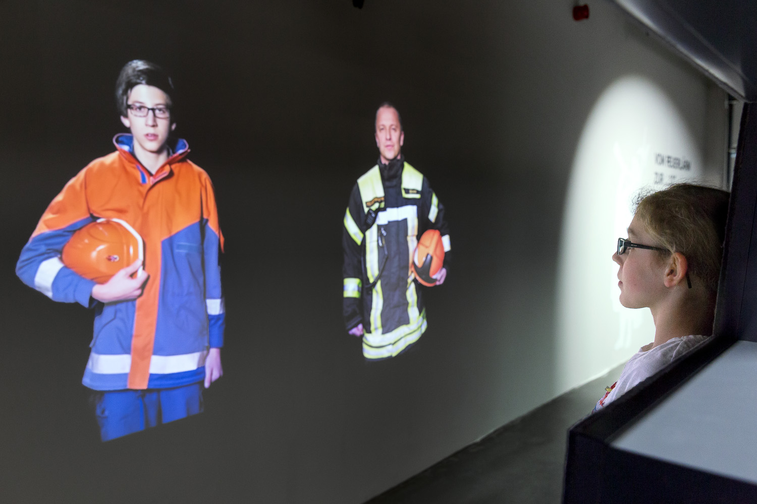 Child looks at projection of a young member of the volunteer fire brigade