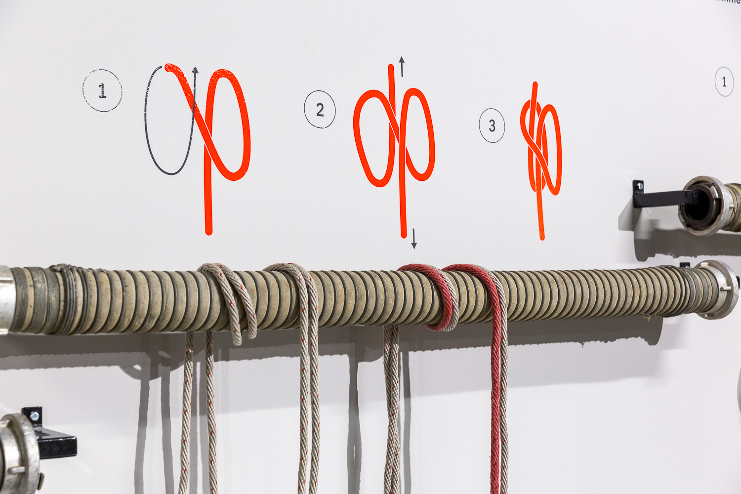 Ropes hang from wall bracket. A simple graphic above shows how to tie a knot