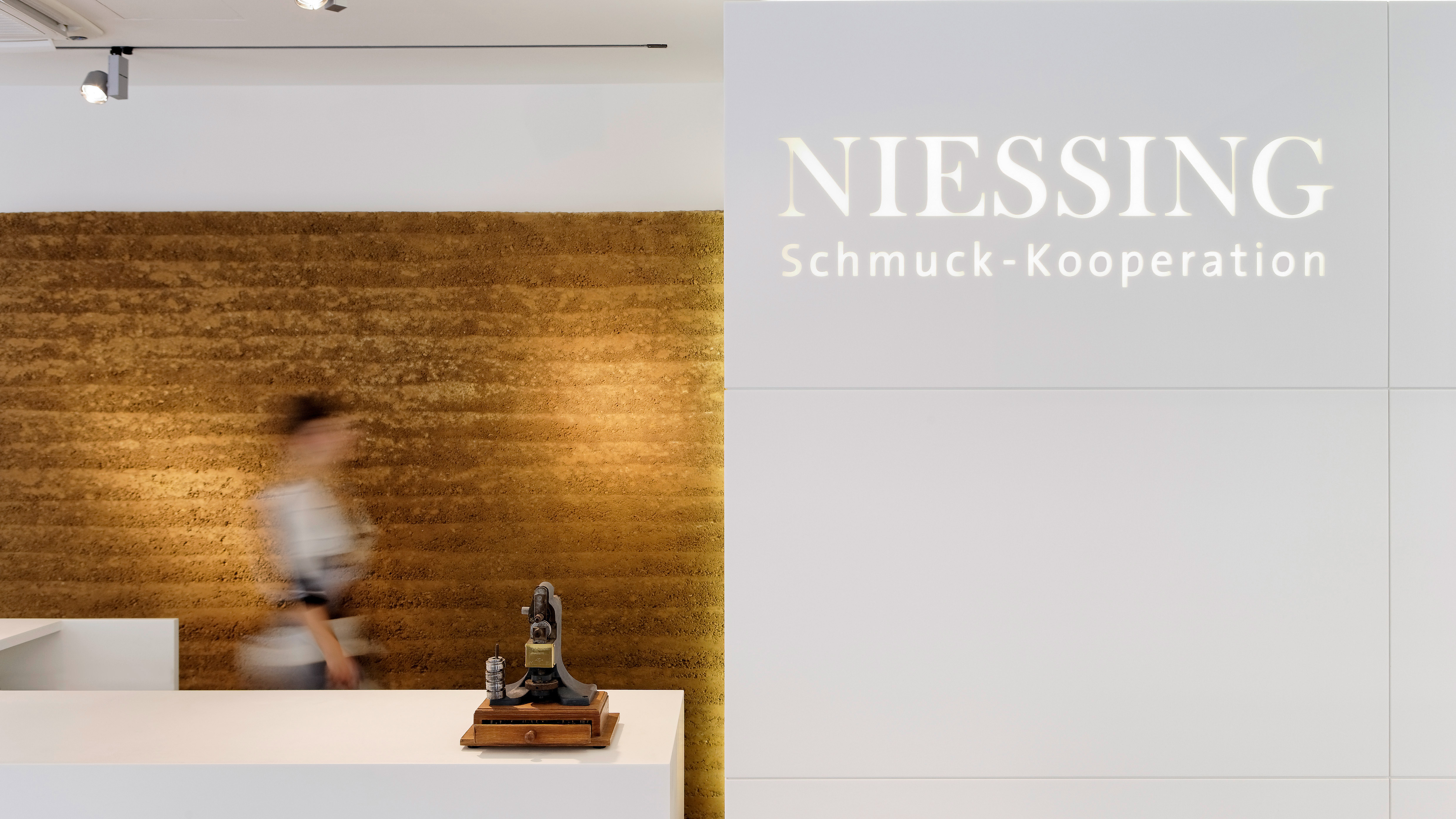 Counter in front of a golden clay wall. Beside: Illuminated Niessing lettering