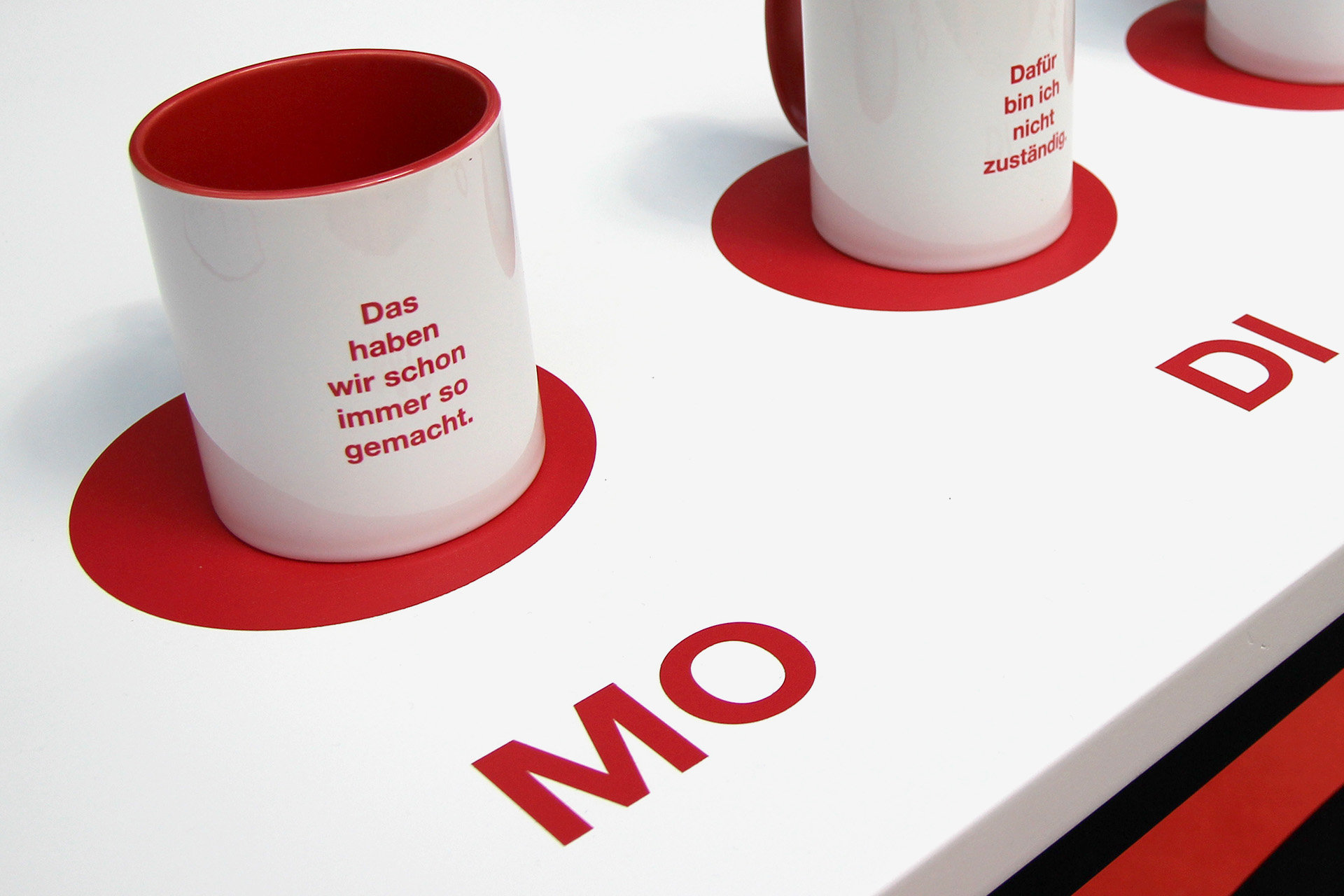 For each weekday a white-red cup with text print of an outdated way of thinking